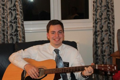Elder Augustine enjoying the guitar at the Blyel home.